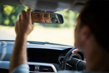 Man adjusting mirror in car