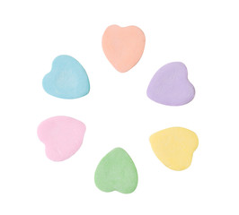 Pastel colored candy hearts arranged in a circle formation isolated on white
