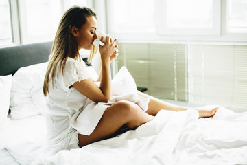 Young woman sitting on a bed and drinking coffee after waking up