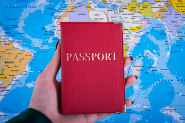 Passport in hand on the background of the map