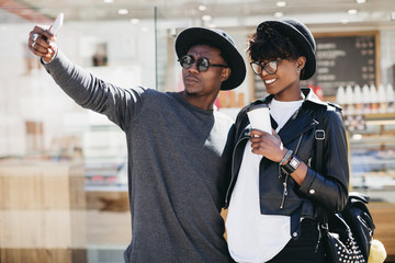 Stylish young african couple in sunglasses drinking coffee and making selfie a street of summer.