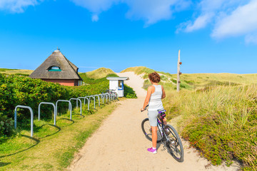 Fototapete - SYLT ISLAND, GERMANY - SEP 6, 2016: young woman on a bike during trip along coast of Sylt island, Germany.