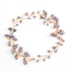 Frame wreath of pale blue dried flowers on white background. Flat lay, top view