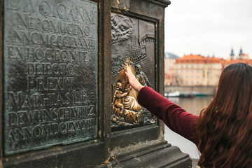 Woman tourist touches a bronze statue of John of Nepomuk on the Charles bridge for good luck. Legends. Prague, Czech Republic