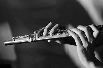 Foto b/n di flauto traverso con due mani che lo tengono