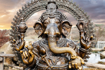 Statue of Hindu Elephant God Ganesha outdoors against dramatic sky