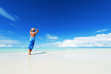 Rear view blonde woman in blue sarong standing on the white sand beach .Copy space