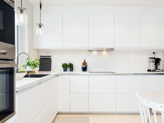 stylish kitchen interior with white cupboards and kitchen counter top