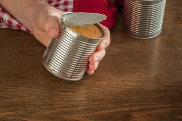 Open a metallic can on the table in the kitchen. Canned food. Condensed milk. Healthy eating and lifestyle.
