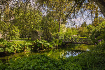 Giardino di Ninfa: piccolo ponte sopra al fiume immerso nella fitta e verde vegetazione