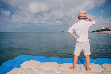 Boy looks on ship on the horizon  from sea pier