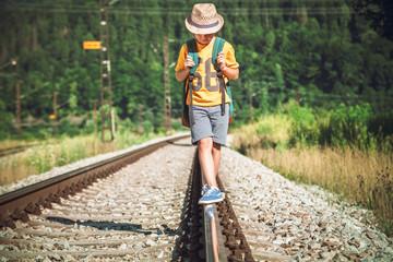 Little boy with backpack walks on railway track