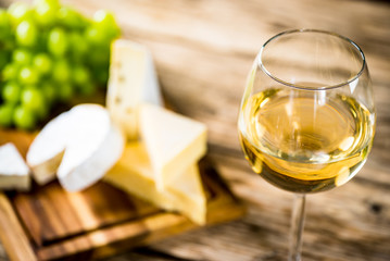 Wine bottles with grapes and cheese on wooden rustic background. copy space Fototapete