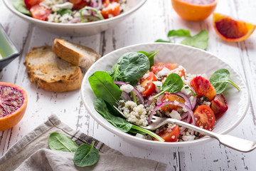 Healthy spring salad with quinoa, fresh spinach and blood oranges on white rustic background