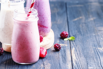 Berry smoothies with yoghurt, gray background, selective focus