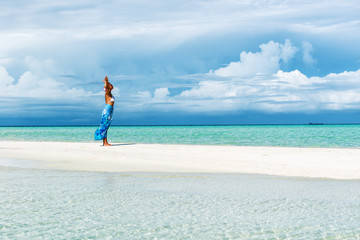 Woman with arms outstretched standing on the white sand beach.Copy space
