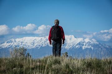 Man hiking with backpack facing mountain range