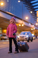 Adorable girl in winter outfit in front of airport building with roller suitcase in night