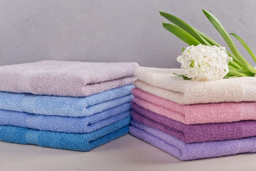 Two stacks of colorful bath towels with hyacinth flower on light background.