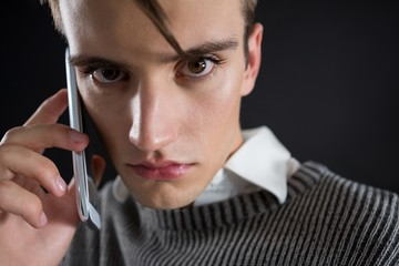 Angry androgynous man talking on mobile phone
