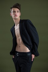 Androgynous man posing against green background