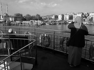 Türkische Frau mit Kopftuch an Bord einer Fähre über den Bosporus von Kadiköy nach Eminönü in Istanbul in der Türkei, fotografiert in traditionellem Schwarzweiss