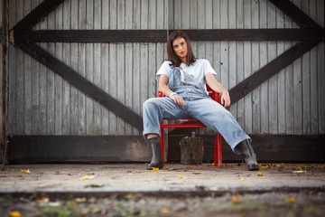 Confident young tomboy girl sitting on a chair in front of the barn on a farm