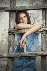 Portrait of beautiful young woman standing in front of rustic wall and leaning on a ladder
