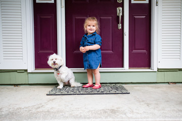 Small child outside door with dog
