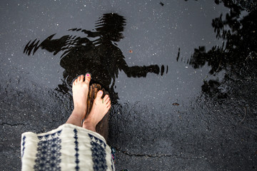 Girl walking in puddle barefoot