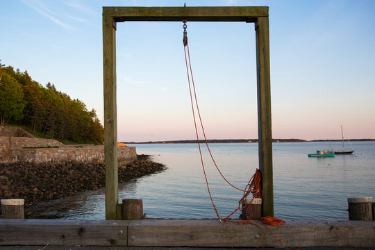 nobody, sunset, wooden, harbour, jetty, pulley, winch, framing, framed, view through, coastal, estuary, water, water surface, diminishing perspective, outdoors, Bar Harbor, Maine, USA,