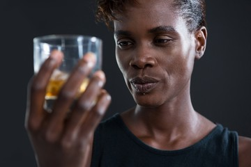 Androgynous man holding whiskey glass