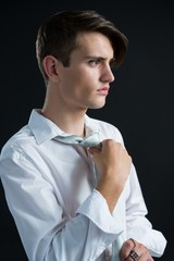 Androgynous man adjusting his tie