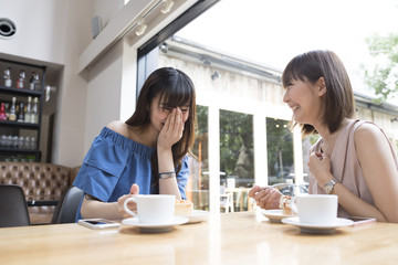 Two women chat with each other happily at the cafe