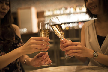 Women are drinking champagne at the bar