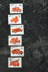Set of lying in a row postage stamps printed in Cuba shows fire engines, series, circa 1977. Copy space for your text on a dark black cement background.