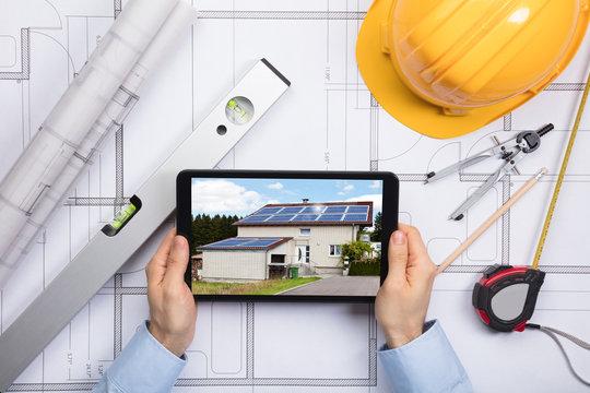 An Architect Using Digital Tablet On Blueprint