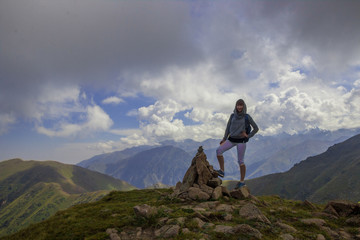 Young woman are standing on top of a mountain and enjoying. Almaty, peak named Furmanov