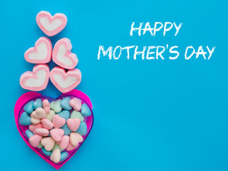 mother's day concept. Marshmallow in a heart frame with Happy mother's day text on blue sky background