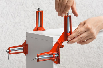 hand installing clamp before furniture assembling