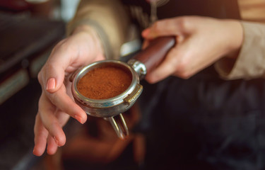 Closeup of female hand with the baristas Holder with freshly ground coffee.