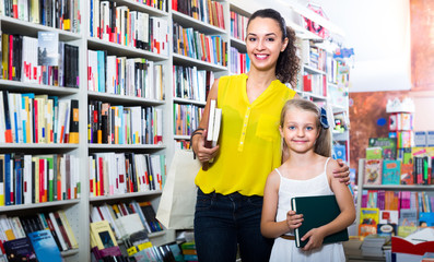 young mother with daughter in book shop.