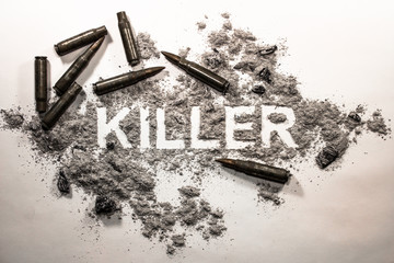 Killer text word written in grey ash, dirt, filth with bullets around as crime, criminal, murder, war, death, violence, weapon, gun concept background