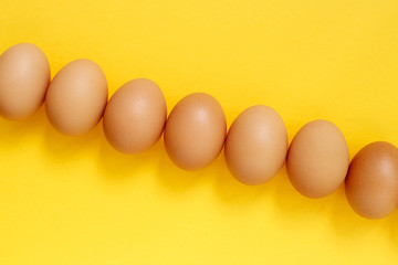 Fresh eggs on yellow background