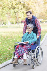 The woman in a wheelchair with her son walking among the park