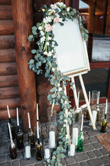 Easel with picture decorated with roses stands before the entrance to the house