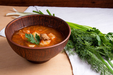 Borsch - traditional Ukrainian and Russian red beetroot soup with red beets in clay bowl on wooden background..