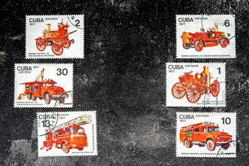 Set of postage stamps printed in Cuba shows fire engines, series, circa 1977. Copy space for your text on a dark black cement background.