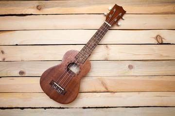 Hawaiian four-stringed ukulele guitar on wooden background