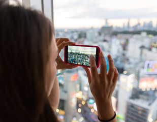 A young woman taking a picture of the city from her hotel room